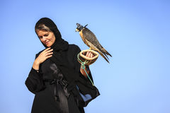 Woman with Peregrine Falcon. A woman in abaya with Peregrine Falcon in Dubai Desert Conservation Reserve, UAE Royalty Free Stock Images