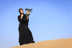 Woman with Peregrine Falcon. A woman in abaya with Peregrine Falcon in Dubai Desert Conservation Reserve, UAE Stock Images