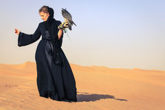 Woman with Peregrine Falcon. Young woman in abaya with Peregrine Falcon in Dubai Desert Conservation Reserve, UAE Stock Photos