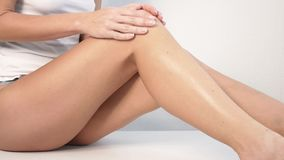 Woman with perfect body applying refreshing cream or body lotion on her legs, Concept depilation, skincare, cosmetics stock footage