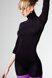 Woman with perfect body dressed in purple striped tights and black top Royalty Free Stock Photography