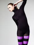 Woman with perfect body dressed in purple striped tights and black top Stock Images