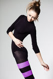 Woman with perfect body jumping dressed in purple striped tights and black top Royalty Free Stock Image