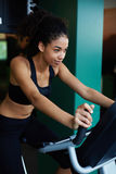 Woman with perfect figure riding on spin bike at fitness center Stock Photos