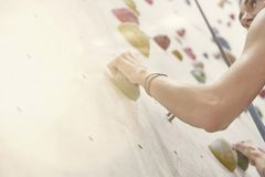 Woman with perfect fit body, beautiful muscular arms, training on a climbing wall in sport hall. Woman with perfect fit body, beautiful muscular arms, training royalty free stock images