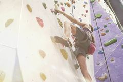 Woman with perfect fit body training on a climbing wall in sport hall, ready to workout. Woman with perfect fit body training on a climbing wall in sport hall royalty free stock image