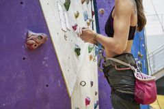 Woman with perfect fit body training on a climbing wall in sport hall, ready to workout. Woman with perfect fit body training on a climbing wall in sport hall royalty free stock photography