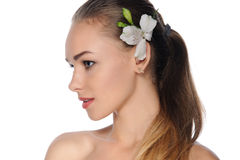 Woman with perfect skin with a white flower in her hair Royalty Free Stock Photos