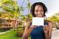 Woman with a perfect smile holds a business card Stock Images