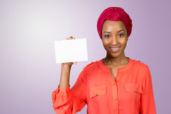 Woman with a perfect smile holds a business card Royalty Free Stock Images