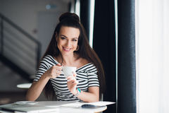 Woman with a perfect smile and white teeth looking at the camera and holding a cup of cappuccino or coffee. Stock Photo