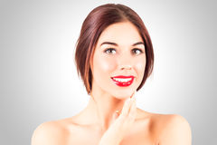 Woman with a perfect smile with white teeth. Sexy woman with red lips touching chin. Royalty Free Stock Image