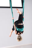 Woman performing an aerial yoga somersault. Upside down woman performing an aerial yoga somersault while suspended from ceiling with green cloth Royalty Free Stock Image