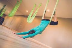 Woman performing antigravity yoga Stock Images
