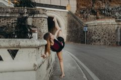 Dancer raising leg while performs classic dance on a road. Royalty Free Stock Image