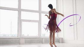 Woman performing dance with ribbon. Slow motion shot of a woman dancing in the studio and performing elements with ribbon stock footage