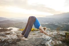 Woman performing downward dog yoga pose outdoors Stock Images