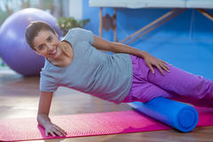 Woman performing exercise using foam roll. Portrait of woman performing exercise using foam roll in the clinic Stock Photography
