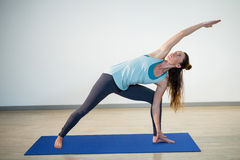 Woman performing extended side angle pose on exercise mat Stock Image