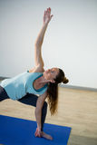 Woman performing extended side angle pose on exercise mat Stock Images