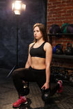 Woman performing front lunge with kettlebells. Young athletic woman performing front lunge with kettlebells at the gym stock photo