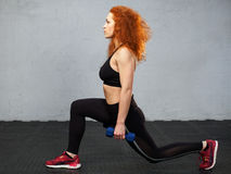 Woman performing frontal lunge. Young ginger woman performing frontal lunge with the dumbbells at the gym stock photo