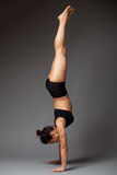 Woman performing handstand. Young athletic  woman in a black top and shorts performing handstand, legs are in the air, side view, gray background Stock Photo