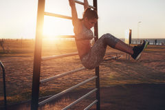 Woman performing hanging leg raises. Candid shot of real healthy and fit woman performing hanging leg raises on outdoor fitness station in sunset at beach royalty free stock images