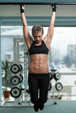 Woman Performing Hanging Leg Raises Exercise Royalty Free Stock Photos