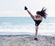 Woman performing a high kick. At the beach working out Stock Image