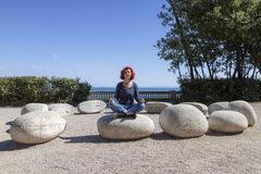 Woman performing joga on energy stones near sea coast Royalty Free Stock Image