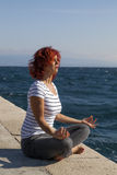 Woman performing joga on sea coast Stock Image