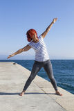 Woman performing joga on sea coast Royalty Free Stock Images