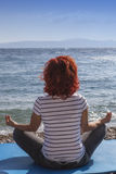 Woman performing joga on sea coast Stock Photos