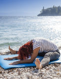 Woman performing joga on sea coast Royalty Free Stock Photography