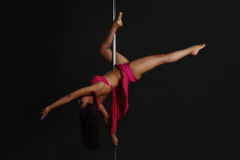 Woman performing pole dance. Beautiful woman performing pole dance, studio shot on black background Royalty Free Stock Photo