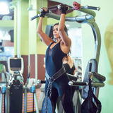 Woman performing pull ups in a bar at gym. Royalty Free Stock Photography