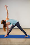 Woman performing triangle pose on exercise mat Stock Image