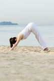 A woman performing yoga on beach. Stock Photography