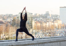 Woman performing yoga in city. Woman in yoga position on wall of urban environment Stock Photos