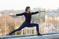 Woman performing yoga in city. Woman in yoga position on wall of urban environment royalty free stock images