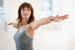 Woman performing yoga in warrior pose Royalty Free Stock Photo