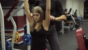 Woman performs a bench press dumbbells over your head, under guidance of a coach. stock video