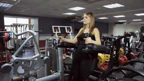 A woman performs an exercise on pumping up press on simulator. Standing in air, back pressed against abutment in back, elbows on elbow rests, grip hand levers stock footage