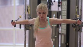 Woman performs exercises on crossover. In gym. Young girl training in gym stock video footage