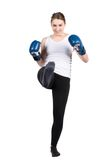 Woman performs kick. Cut out image of a young kickboxing woman with blue boxing gloves who is performing a kick forward Stock Photos