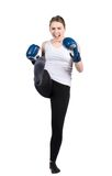 Woman performs kick. Cut out image of a young kickboxing woman with blue boxing gloves who is performing a kick forward Stock Photography