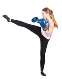 Woman performs kick. Cut out image of a young kickboxing woman with blue boxing gloves who is performing a kick to the left Stock Images