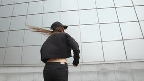 Woman performs modern hip-hop dance against metal wall contemporary freestyle, urban environmen