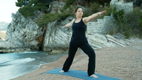 Woman performs pose of warrior in yoga against background of sea rocks. Grown-up lady stands on her feet and stretches hands out on beach in solitude stock footage